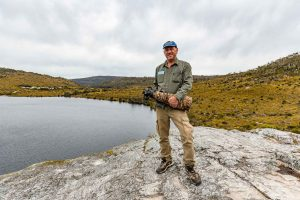 Kape Images founder, Peter Rowland, standing on a rock platform next to Dove Lake in Tasmania, holding his camera