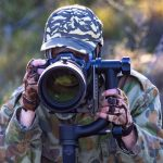 Wildlife Photographer Jess Steele wearing camouflage clothing and looking through the lens of her camera